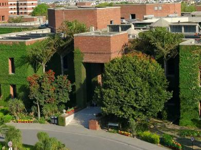 picture of LUMS academic block's red brick building covered with vines